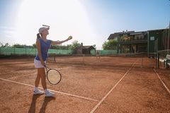 Härlig ung kvinna som spelar tennis och portionen royaltyfri bild