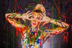 Härlig ung kvinna som täckas med målarfärger Royaltyfri Fotografi