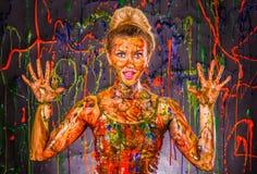 Härlig ung kvinna som täckas med målarfärger Fotografering för Bildbyråer