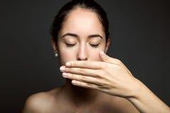 Härlig ung kvinna som täcker hennes mun med handen isolerat Royaltyfri Fotografi