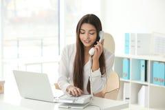 Härlig ung kvinna som talar vid telefonen, medan arbeta i regeringsställning arkivbild