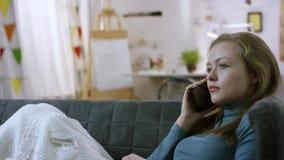Härlig ung kvinna som tar en påringning på smartphonen, medan ligga på en soffa lager videofilmer