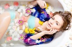 Härlig lady som tar ett bad med blommapetals Arkivbild