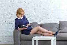 Härlig ung kvinna som tycker om en bok som ligger på en soffa fotografering för bildbyråer