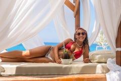 Härlig ung kvinna som tycker om en coctail i en cabana arkivfoton