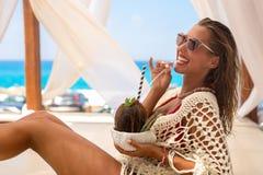 Härlig ung kvinna som tycker om en coctail i en cabana fotografering för bildbyråer