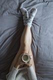 Härlig ung kvinna som tycker om kaffe på säng i hennes sovrum Hom Royaltyfria Bilder