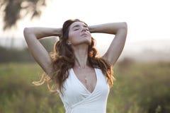 Härlig ung kvinna som tycker om solnedgång i fältet Fotografering för Bildbyråer