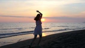 Härlig ung kvinna som tycker om solnedgången på stranden arkivfilmer