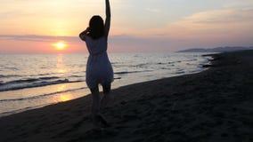 Härlig ung kvinna som tycker om solnedgången på stranden stock video
