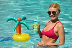 Härlig ung kvinna som tycker om varm solig dag i simbassängen royaltyfri fotografi