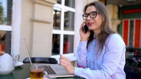 Härlig ung kvinna som utomhus arbetar och talar på en smartphone i ett kafé lager videofilmer