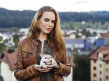 Härlig ung kvinna som utomhus dricker kaffe Fotografering för Bildbyråer