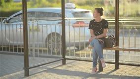 Härlig ung kvinna som väntar offentligt trans. på stationen för stads- inställning och ser hennes klocka arkivfilmer