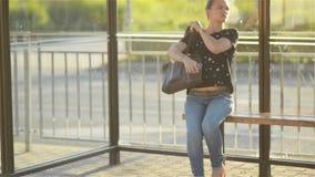 Härlig ung kvinna som väntar offentligt trans. på stationen och att lämna för stads- inställning lager videofilmer