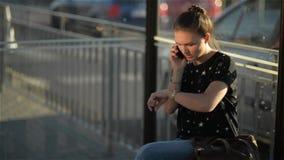Härlig ung kvinna som väntar på en buss och ser hennes klocka, flicka som talar på mobiltelefonen, medan vänta offentligt stock video