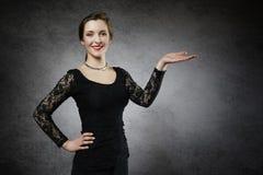 Härlig ung kvinna som visar din produkt Arkivbild