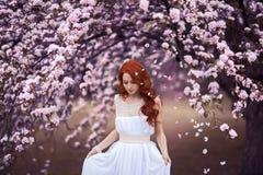 Härlig ung kvinna under blomningträdet arkivbilder