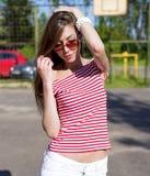 Härlig ung kvinna, vilar utomhus som den ljusa röda T-tröja, modestil, lycklig brunetthåruträtning Royaltyfri Bild
