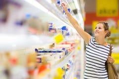 Härlig ung kvinnashopping för dagbokprodukter på en livsmedelsbutik royaltyfria foton
