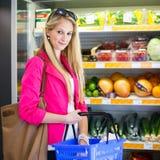 Härlig ung kvinnashopping i en livsmedelsbutik/en supermarket Royaltyfri Foto