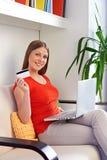 Kvinnashopping med bärbar dator och kreditkorten Arkivfoton