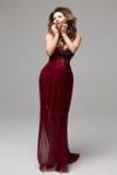 Härlig ung kvinnlig I i en lång röd klänning med ädelstenar på en grå bakgrund Klädkatalog, katalogdesign Royaltyfria Bilder