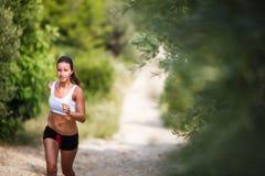 Härlig ung kvinnlig löpare på en skogbana, på en älskvärd summ royaltyfri bild