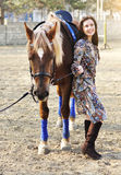 Härlig ung kvinnlig som går med hennes bruna häst i en bygd Royaltyfri Foto
