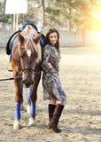 Härlig ung kvinnlig som går med hennes bruna häst i en bygd Royaltyfria Foton