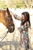 Härlig ung kvinnlig som går och smeker hennes bruna häst i en bygd Arkivbild