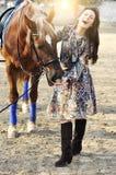 Härlig ung kvinnlig som går och smeker hennes bruna häst i en bygd Arkivbilder