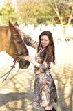 Härlig ung kvinnlig som går och smeker hennes bruna häst i en bygd Fotografering för Bildbyråer