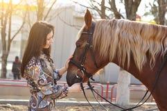 Härlig ung kvinnlig som går och smeker hennes bruna häst i en bygd Royaltyfri Bild