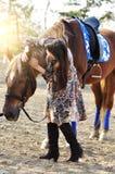 Härlig ung kvinnlig som går och smeker hennes bruna häst i en bygd Royaltyfria Bilder