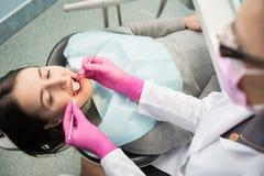 Härlig ung kvinnlig som har den tand- kontrollen upp i tand- kontor Tandläkare undersökande tänder för patient` ett s arkivbild