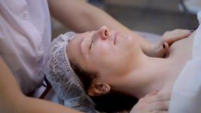 Härlig ung kvinnlig som kopplar av den kvinnliga mottagande ansikts- massagen, skönhetbrunnsort stock video