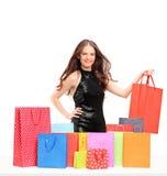 Härlig ung kvinnlig som poserar med färgrika shoppingpåsar Arkivfoto