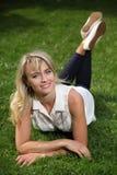Härlig ung långhårig blondin som poserar för kameran som ligger på gräs Arkivfoto