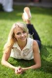 Härlig ung långhårig blondin som poserar för kameran som ligger på gräs Royaltyfri Fotografi