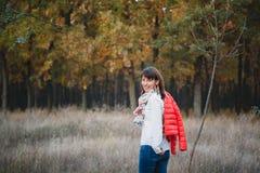 Härlig ung le kvinna i det utomhus- jeans och ljusa omslaget Arkivfoto