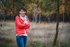 Härlig ung le kvinna i det utomhus- jeans och ljusa omslaget Royaltyfria Foton