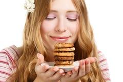 Härlig ung le kvinna med kakor arkivbilder