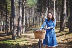 Härlig ung le kvinna med kort mörkt hår och hatten som står nära cykeln med korgen av den enorma buketten av Arkivfoto