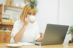 Härlig ung le kvinna som arbetar på bärbara datorn, medan tycka om dricka varmt kaffesammanträde i en vardagsrum hemma enjoying royaltyfria bilder