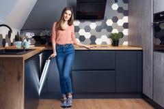Härlig ung le kvinna som gör disk i köket arkivbilder