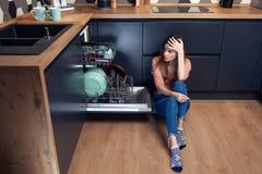Härlig ung le kvinna som gör disk i köket royaltyfri foto