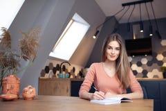 Härlig ung le kvinna som hemifrån arbetar royaltyfri bild