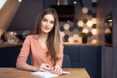 Härlig ung le kvinna som hemifrån arbetar arkivfoton