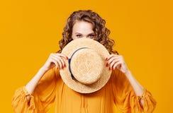 Härlig ung lockig kvinna i sommarhatt på gul bakgrund fotografering för bildbyråer